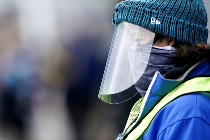 A security person stands in the Bank of America Stadium during a global pandemic before the first half of an NFL football game between the Carolina Panthers and the Tampa Bay Buccaneers, Sunday, Nov. 15, 2020, in Charlotte , N.C. (AP Photo/Gerry Broome)