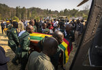 The casket of former president Robert Mugabe is carried into an air force helicopter for transport to a stadium where it will lie in state, as his widow Grace Mugabe wears a black veil, in background, at his official residence in the capital Harare, Zimbabwe Thursday, Sept. 12, 2019. Controversy over where and when Robert Mugabe will be buried has overshadowed arrangements for Zimbabweans to pay their respects to the deceased leader. (AP Photo/Ben Curtis)
