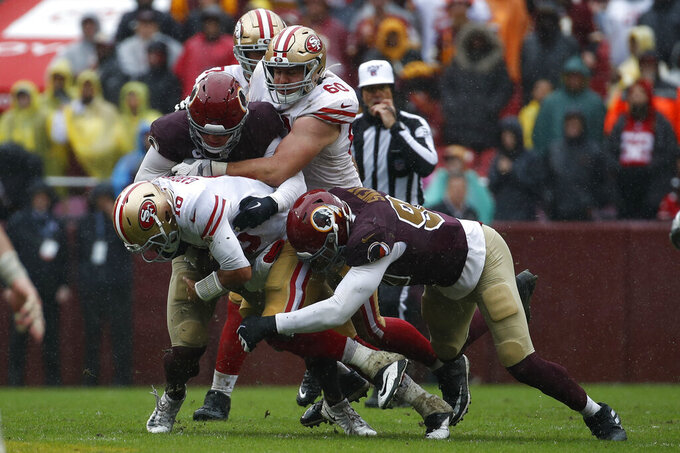 San Francisco 49ers quarterback Jimmy Garoppolo (10) is sacked by Washington Redskins linebackers Ryan Kerrigan, left, and Montez Sweat in the first half of an NFL football game, Sunday, Oct. 20, 2019, in Landover, Md. (AP Photo/Alex Brandon)