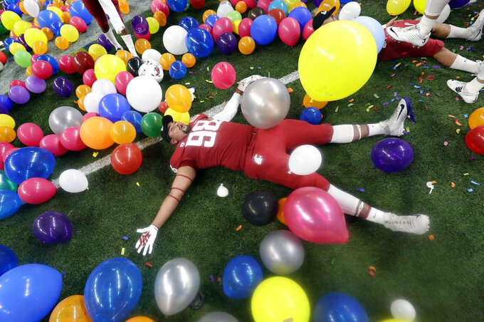 Washington State defensive lineman Dallas Hobbs rolls between balloons as he he celebrates the team's 28-26 win over Iowa State in the Alamo Bowl NCAA college football game Friday, Dec. 28, 2018, in San Antonio. (AP Photo/Eric Gay)