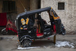 In this Nov. 19, 2019 photo, a tuk-tuk driver washes his vehicle in an alleyway of a slum in Cairo, Egypt. Motorized rickshaws known as tuk-tuks have ruled the streets of Cairo's slums for the past two decades hauling millions of Egyptians home every day. Now the government is taking its most ambitious stand yet against the polluting three-wheeled vehicles: to modernize the neglected transport system, it plans to replace tuk-tuks with clean-running minivans. (AP Photo/Nariman El-Mofty)