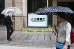 People walk past the company sign of the Mitsubishi Heavy Industries in Tokyo Tuesday, July 16, 2019. Colonial-era Korean laborers are seeking a court approval for the sales of local assets of their former Japanese company as it is refusing to compensate them. Lawyers for Koreans who worked for the Japanese company say they'll soon request a South Korean court to authorize the sales of some of Mitsubishi's seized assets in South Korea. (AP Photo/Koji Sasahara)