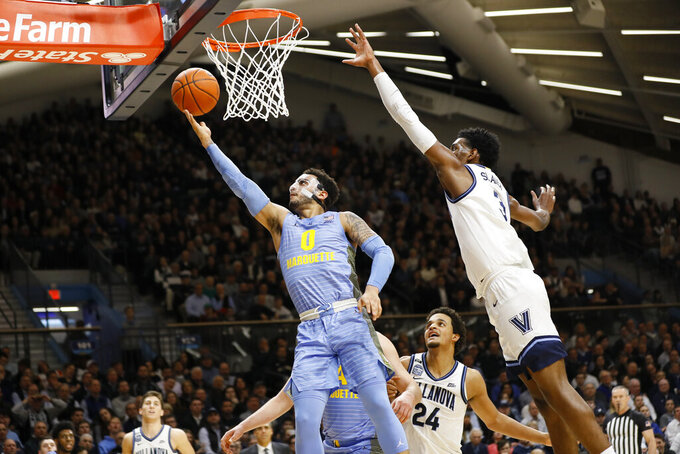 Marquette's Markus Howard (0) goes up for a shot next to Villanova's Brandon Slater (3) during the first half of an NCAA college basketball game Wednesday, Feb. 12, 2020, in Villanova, Pa. (AP Photo/Matt Slocum)