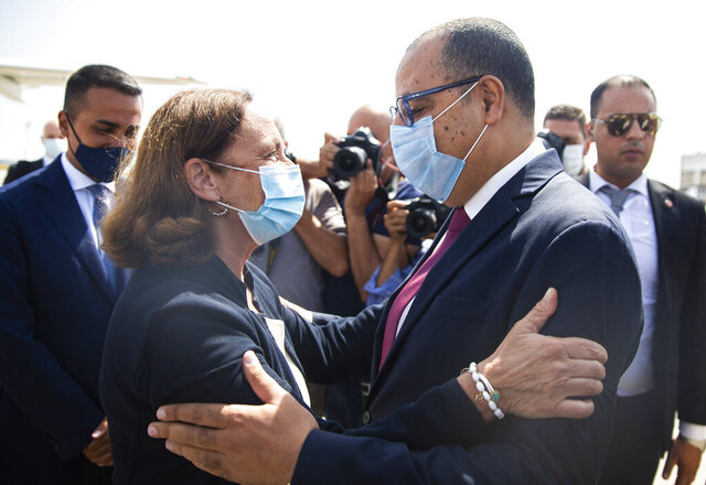 Tunisian Interior and Prime Minister designate Hichem Mechichi, right, greets Italian Interior Minister Luciana Lamorgese at Tunis Carthage airport in Tunis, Monday, Aug, 17, 2020. Top Italian and EU officials are holding talks in Tunisia on Monday to try to stem the growing numbers of migrants crossing from this North African country to Europe. (AP Photo/Riadh Dridi)