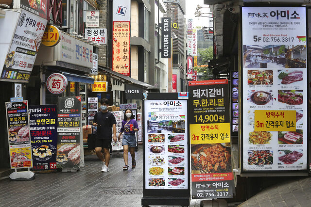 People wearing face masks to help protect against the spread of the coronavirus pass by banners showing the menu items of restaurants in Seoul, South Korea, Friday, Aug. 28, 2020. South Korean officials are considering reducing working hours of restaurants and cafes as the country counted its 15th straight day of triple-digit jumps in coronavirus infections. (AP Photo/Ahn Young-joon)