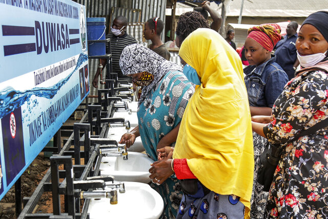 In this photo taken Monday, May 18, 2020, people use a hand-washing station installed for members of the public entering a market in Dodoma, Tanzania. As of late May 2020, the country's number of confirmed coronavirus cases hasn't changed for three weeks, and the international community is openly worrying that Tanzania's government is hiding the true scale of the pandemic. (AP Photo)