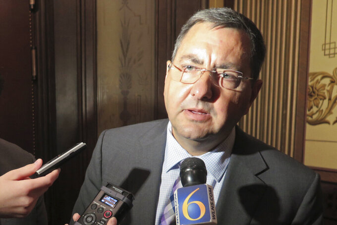 FILE - in this Oct. 19, 2016, file photo, state Sen. Jim Stamas, speaks outside the Michigan Senate chamber in Lansing, Mich. Michigan will make more kids eligible for child care subsidies, equip all state troopers with body cameras and make permanent a pandemic wage hike for nursing home workers and other caregivers under the next state budget, poised for initial approval Tuesday, Sept. 21, 2021. (AP Photo/David Eggert, File)