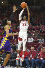 Arkansas guard Jimmy Whitt Jr. (33) shoots over LSU defender Trendon Watford (2) during the first half of an NCAA college basketball game Wednesday, March 4, 2020, in Fayetteville, Ark. (AP Photo/Michael Woods)