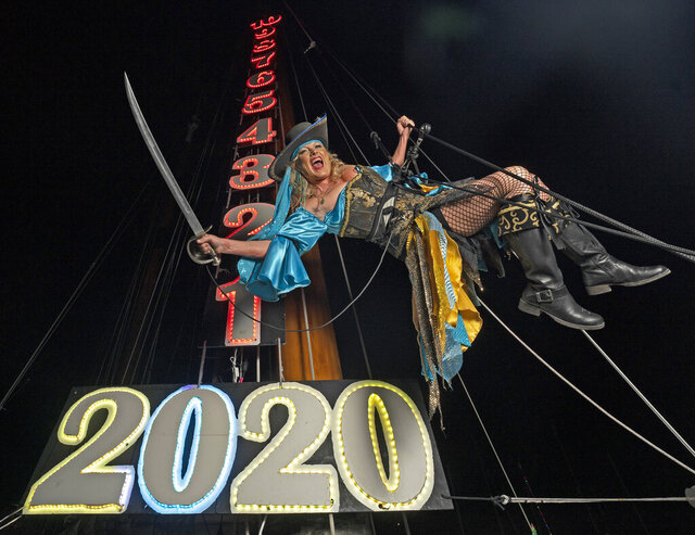 In this photo provided by the Florida Keys News Bureau, Evalena Worthington rehearses her New Year's Eve descent, costumed as a pirate wench, late Monday, Dec. 30, 2019, in Key West, Fla. Worthington's event, at the Schooner Wharf Bar, is one of six offbeat warm-weather takeoffs on New York City's Times Square