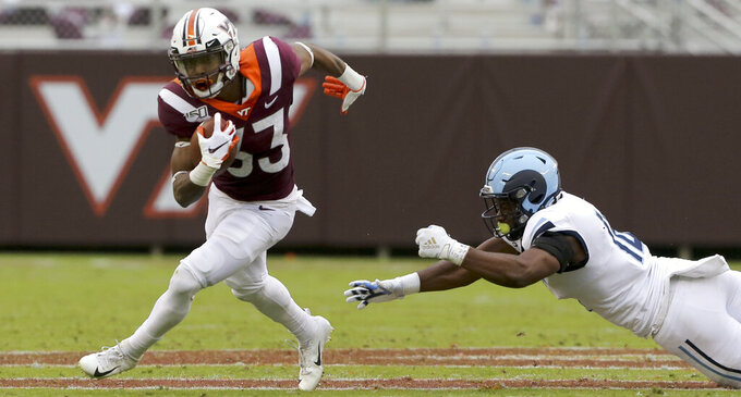 Virginia Tech running back Deshawn McClease (33) escapes Rhode Island defender Branyan Javier- Castillo (16) in the first half of an NCAA college football game in Blacksburg Va., Saturday, Oct. 12 2019. (Matt Gentry/The Roanoke Times via AP)