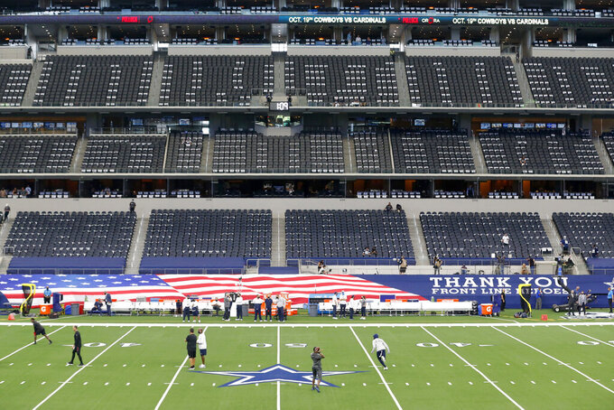 Members of the Dallas Cowboys and Atlanta Falcons warm up in front of nearly empty seats before an NFL football game in Arlington, Texas, Sunday, Sept. 20, 2020. (AP Photo/Michael Ainsworth)