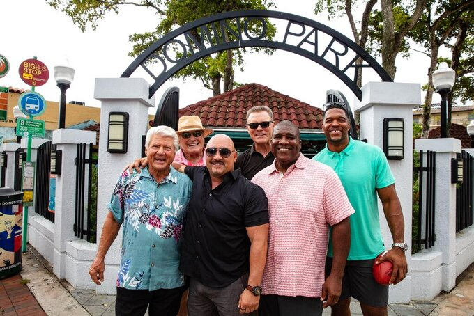 "Jimmy Johnson, Terry Bradshaw, Jay Glazer, Howie Long, Curt Menefee and Michael Strahan, from left, pose in Domino Park in Miami on Aug. 23, 2019. The ""Fox NFL Sunday"" pregame show was inducted into the NAB Broadcasting Hall of Fame in April and starts its 26th season on Sunday, Sept. 8. (Fox Sports via AP)"