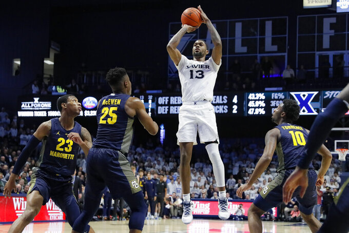 Xavier's Naji Marshall (13) shoots over Marquette's Koby McEwen (25) during the second overtime in an NCAA college basketball game Wednesday, Jan. 29, 2020, in Cincinnati. (AP Photo/John Minchillo)