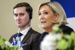 Jaak Madison of Estonian Conservative People's Party, left, looks at Leader of the French National Front Marine Le Pen during a news conference in Tallinn, Estonia on Tuesday, May 14, 2019. (AP Photo/Hendrik Osula)