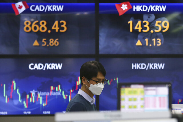 A currency trader watches monitors at the foreign exchange dealing room of the KEB Hana Bank headquarters in Seoul, South Korea, Thursday, Jan. 28, 2021. Asian shares skidded on Thursday as a reality check set in about longtime economic damage from the coronavirus pandemic, giving Wall Street its worst day since October.(AP Photo/Ahn Young-joon)
