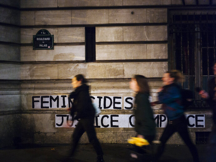 In this Nov. 4 2019 photo, Lea, Pauline and Clivia, from left, walk past a slogan they recently pasted on walls of the Palais de Justice courthouse reading