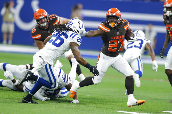 Cleveland Browns running back Kareem Hunt (27) tries to get past Indianapolis Colts strong safety Clayton Gathers (26) during the first half of an NFL preseason football game in Indianapolis, Saturday, Aug. 17, 2019. (AP Photo/Michael Conroy)