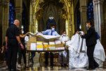 Organizers cover the boxed cremated remains of Mexicans who died from COVID-19 before a service at  St. Patrick's Cathedral, Saturday, July 11, 2020, in New York. The ashes were blessed before they were repatriated to Mexico. (AP Photo/Eduardo Munoz Alvarez)