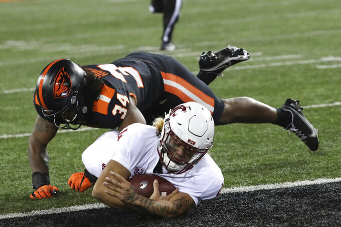Washington State quarterback Jayden de Laura (4) slides into the end zone, under Oregon State inside linebacker Avery Roberts (34) during the second half of an NCAA college football game in Corvallis, Ore., Saturday, Nov. 7, 2020. Washington State won 38-28. (AP Photo/Amanda Loman)