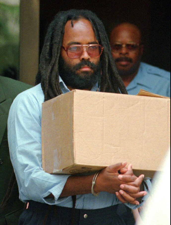 FILE - In this July 12, 1995 file photo, Mumia Abu-Jamal leaves Philadelphia's City Hall after a hearing. A federal appeals court is keeping alive a lawsuit brought by Abu-Jamal, convicted of killing a Philadelphia police officer in 1981, over his lack of access in prison to hepatitis drugs. The 3rd U.S. Circuit Court of Appeals on Friday, JULY 19, 2019, upheld a lower-court decision that Corrections Department employees were not immune to being sued over their decisions regarding the 65-year-old Abu-Jamal. Abu-Jamal says his initial denial of treatment with two antiviral drugs violated his constitutional right to be free from cruel and unusual punishment. He previously won a court order to provide the treatment. (AP Photo/Chris Gardner, File)