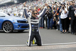 """FILE - In this May 26, 2013, file photo, Tony Kanaan, of Brazil, celebrates on the start/finish line after winning the Indianapolis 500 auto race at the Indianapolis Motor Speedway in Indianapolis, Kanaan will get to race 5 oval events, including the Indianapolis 500, in what will be called his """"farewell tour"""" this upcoming IndyCar season. (AP Photo/Tom Strattman, File)"""
