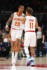 Atlanta Hawks forward John Collins (20) reacts with guard Trae Young (11) in the first half of an NBA basketball game against the Boston Celtics on Monday, Feb. 3, 2020, in Atlanta. (AP Photo/Todd Kirkland)