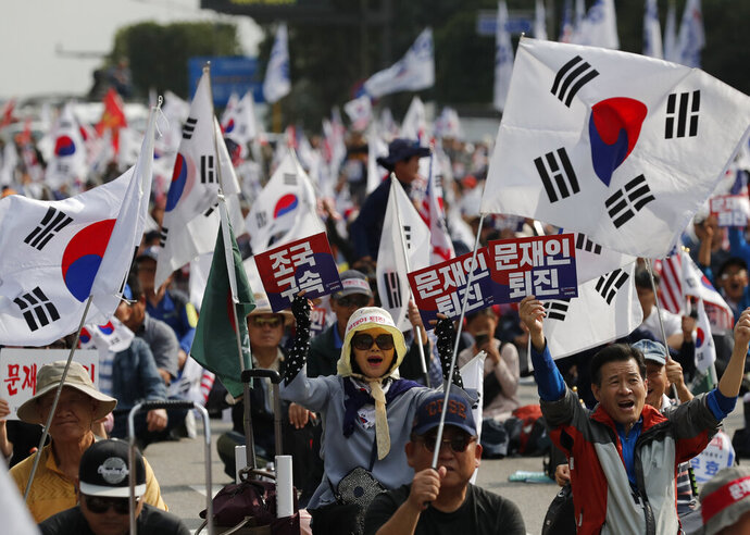 Protesters shout slogans as they wave national flags and signs during a rally denouncing South Korea's Justice Minister Cho Kuk in Seoul, South Korea, Saturday, Oct. 5, 2019. The letters read