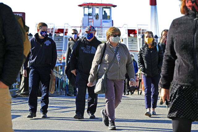 Commuters from Peaks Island arrive on the mainland, Thursday, May 21, 2020, in Portland, Maine. Ferry passengers are required to wear masks during the coronavirus pandemic. (AP Photo/Robert F. Bukaty)