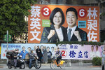 In this Thursday, Jan. 9, 2020, photo, Taiwanese residents pass by campaign billboard with photo of Taiwan president Tsai Ing-wen in Taipei, Taiwan. Taiwan's ruling party is crying foul over alleged Chinese attempts to sway the self-governing island's presidential election on Saturday. The Democratic Progressive Party, known as the DPP, rushed through a law banning