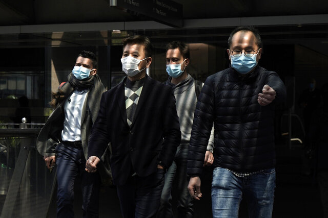 People wearing masks, walk in Central, a business district in Hong Kong, Wednesday, Feb. 19, 2020. Russia says it will temporarily ban Chinese nationals from entering the country amid the outbreak of the new virus centered in China that has infected more than 73,000 people. (AP Photo/Kin Cheung)