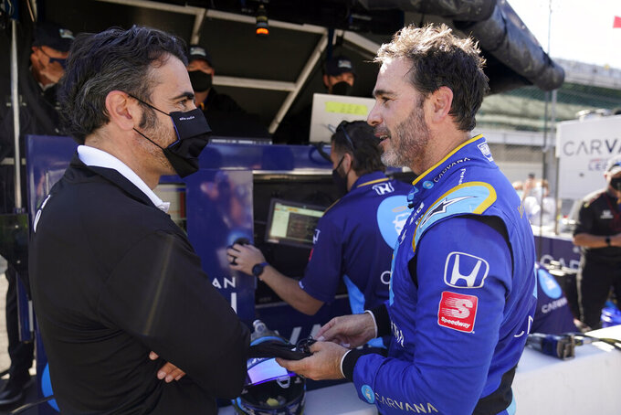 FILE - In this May 14, 2021, file photo, Jimmie Johnson, right, talks with Dario Franchitti following a practice session for the IndyCar auto race at Indianapolis Motor Speedway in Indianapolis. Johnson is hopeful of testing in August at Homestead-Miami Speedway as part of a path toward running in the Indianapolis 500 in 2022. The seven-time NASCAR champion jumped this season to IndyCar and has competed in seven races for team owner Chip Ganassi. (AP Photo/Darron Cummings, File)