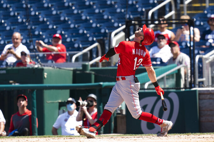 Cincinnati Reds' Tyler Naquin (12) follows the ball and flies out during the sixth inning of the resumption of a rain-delayed baseball game against the Washington Nationals in Washington, Thursday, May 27, 2021.  (AP Photo/Manuel Balce Ceneta)