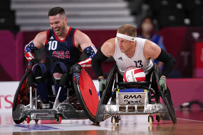 Britain's Aaron Phipps, right, moves the ball against Joshua Wheeler of the United States during the wheelchair rugby gold medal match at the Tokyo 2020 Paralympic Games, Sunday, Aug. 29, 2021, in Tokyo, Japan. (AP Photo/Shuji Kajiyama)