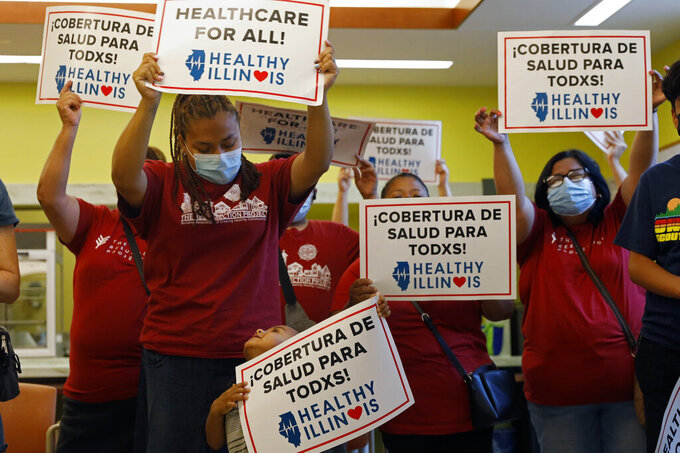 Members of Health Illinois coalition celebrate the extension of state health insurance coverage to older immigrants, ages 55 and over, living in the country illegally, Tuesday, July 20, 2021, in Chicago's Pilsen neighborhood. The state was the first nationwide to offer a Medicaid-like program for immigrant seniors last year and used this year's budget to expand the program. (AP Photo/Shafkat Anowar)