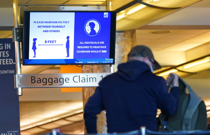 "FILE - In this Thursday, Dec. 31, 2020 file photo, an electronic sign advises travelers to wear face masks and practice social distancing while passing through the main terminal of Denver International Airport in Denver. On Friday, April 9, 2021, The Associated Press reported on stories circulating online incorrectly asserting the federal government wants to require Americans to present a health passport or vaccine certificate ""on demand,"" including for domestic travel. While private businesses are considering vaccine passports for certain activities, Biden administration officials have said the federal government will not mandate vaccine passports. (AP Photo/David Zalubowski)"