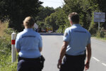 French gendarmes block the road leading the site of a jet crash near Pluvigner, western France, Thursday, Sept.19, 2019. A Belgian F-16 fighter jet crashed in western France, damaging a house, setting a field ablaze and leaving a pilot suspended for two hours from a high-voltage electricity line after his parachute got caught, according to French authorities. (AP Photo/David Vincent)
