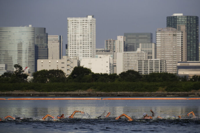 "FILE - In this Aug. 11, 2019, file photo, athletes compete in a marathon swimming test event at Odaiba Marine Park, a venue for marathon swimming and triathlon at the Tokyo 2020 Olympics, in Tokyo. The IOC moved next year's Tokyo Olympic marathons and race walks out of the Japanese capital to avoid the stifling heat and humidity. Some swimmers and an 11,000-member coaching body want similar treatment: find an alternative to the distance-swimming venue in Tokyo Bay known as the ""Odaiba Marine Park.""(AP Photo/Jae C. Hong, File)"