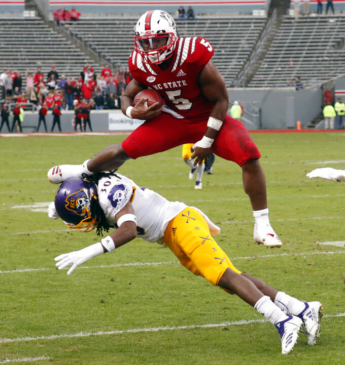 North Carolina State's Damontay Rhem (5) hurdles over East Carolina's Gerard Stringer (30) as he runs upfield during the second half of NCAA college football game in Raleigh, N.C., Saturday, Dec. 1, 2018. N.C. (AP Photo/Chris Seward)