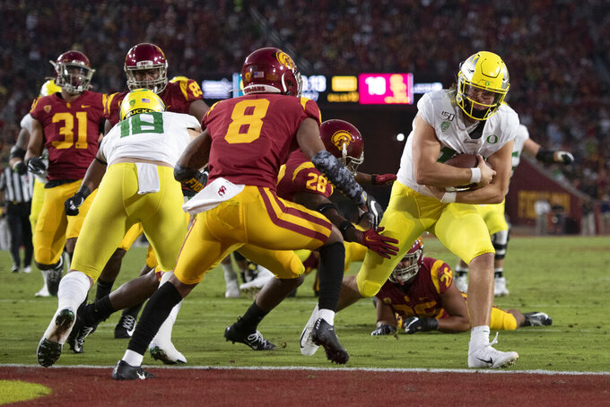 Oregon quarterback Justin Herbert, right, sprints to score a touchdown as Southern California cornerback Chris Steele (8) looks on during the first half of an NCAA college football game Saturday, Nov. 2, 2019, in Los Angeles. (AP Photo/Kyusung Gong)