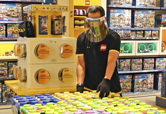FILE - In this Monday, June 15, 2020 file photo, an employee wearing protective gear arrange boxes of Lego at a toy store at the Senayan City, in Jakarta, Indonesia. Sales of Lego sets surged in 2020 as more children stayed home during global pandemic lockdowns - and parents bought the colorful plastic brick toys to keep them entertained during weeks of isolation. The privately-held Danish company said its net profit rose 19% to 9.9 billion kroner ($1.6 billion) as sales jumped 21% and it grew its presence in its 12 largest markets. (AP Photo/Tatan Syuflana, file)