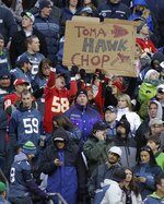 """FILE - In this Nov. 28, 2010, file photo, Kansas City Chiefs fans hold a sign that reads """"TomaHAWK Chop,"""" during an NFL football game between the Chiefs and the Seattle Seahawks in Seattle. The Kansas City Chiefs barred headdresses and war paint amid the nationwide push for racial justice, but its effort to make its popular """"war chant"""" more palatable is getting a fresh round of scrutiny from Native American groups as the team prepares to make its second straight Super Bowl appearance.  (AP Photo/Ted S. Warren, File)"""
