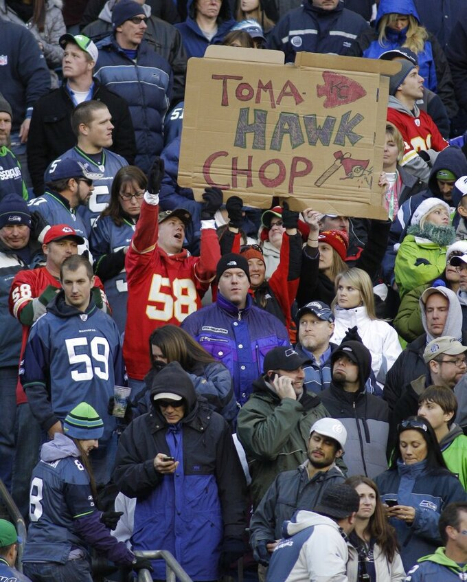 "FILE - In this Nov. 28, 2010, file photo, Kansas City Chiefs fans hold a sign that reads ""TomaHAWK Chop,"" during an NFL football game between the Chiefs and the Seattle Seahawks in Seattle. The Kansas City Chiefs barred headdresses and war paint amid the nationwide push for racial justice, but its effort to make its popular ""war chant"" more palatable is getting a fresh round of scrutiny from Native American groups as the team prepares to make its second straight Super Bowl appearance.  (AP Photo/Ted S. Warren, File)"