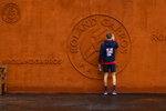 A ball boy touches the tournament logo prior to posing for pictures during second round matches of the French Open tennis tournament at the Roland Garros stadium in Paris, France, Wednesday, Sept. 30, 2020. (AP Photo/Peter Dejong)