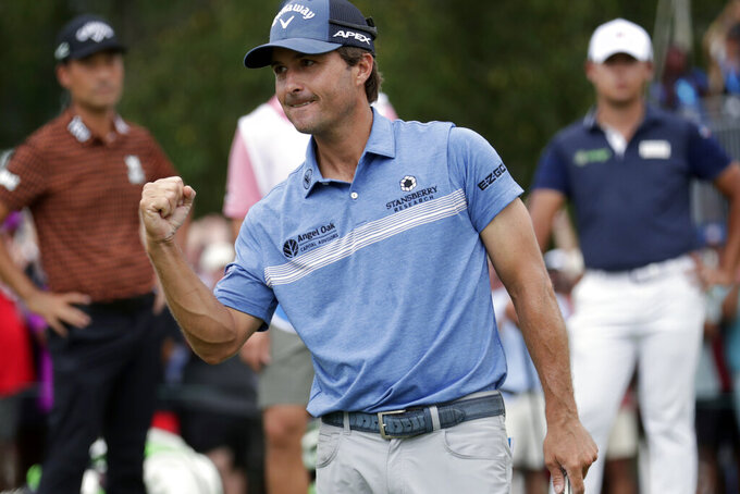 Kevin Kisner celebrates after making a birdie putt on the second playoff hole on the 18th green to win the Wyndham Championship golf tournament at Sedgefield Country Club in Greensboro, N.C., Sunday, Aug. 15, 2021. Other players, background, in the playoff look on. (AP Photo/Chris Seward)
