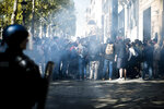 Demonstrators take cover from tear gas fired by riot police officers during a yellow vest demonstration, in Paris, Saturday, Sept 21. 2019. Paris police have used tear gas to disperse anti-government demonstrators who try to revive the yellow vest movement in protest at perceived economic injustice and French President Emmanuel Macron's government. The French capital was placed under high security as few hundred anti-government protesters started marching in the Paris streets. (AP Photo/Kamil Zihnioglu)