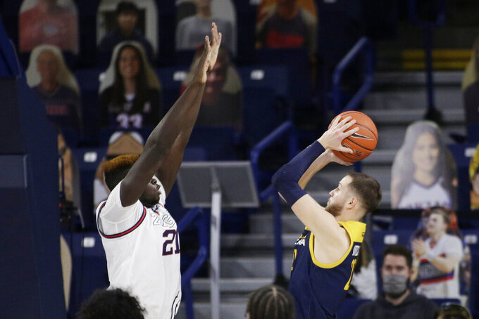 Northern Arizona guard Luke Avdalovic, right, shoots while pressured by Gonzaga center Oumar Ballo during the second half of an NCAA college basketball game in Spokane, Wash., Monday, Dec. 28, 2020. Gonzaga won 88-58. (AP Photo/Young Kwak)