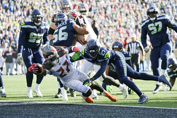 Tampa Bay Buccaneers running back Ronald Jones, lower left, scores a touchdown ahead of Seattle Seahawks defensive back Marquise Blair, center right, during the first half of an NFL football game, Sunday, Nov. 3, 2019, in Seattle. (AP Photo/John Froschauer)