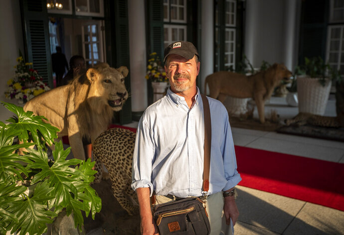 In this photo taken Sept. 13, 2019, Associated Press journalist Andrew Meldrum poses for a photograph at the entrance to State House in the capital Harare, Zimbabwe. After 16 years in journalistic exile, Meldrum returned to Zimbabwe, the country where he worked as a journalist for 23 years until he was expelled by former president Robert Mugabe's government. For the past week he reported on the mourning period for Mugabe. (AP Photo/Ben Curtis)