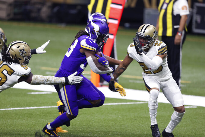 Minnesota Vikings running back Dalvin Cook (33) carries against New Orleans Saints cornerback Marshon Lattimore (23) and outside linebacker Demario Davis on a 15 yard touchdown run in the first half of an NFL football game in New Orleans, Friday, Dec. 25, 2020. (AP Photo/Butch Dill)