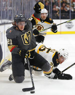 Vegas Golden Knights center Cody Eakin (21) vies for the puck with Boston Bruins defenseman Brandon Carlo (25) during overtime in an NHL hockey game Wednesday, Feb. 20, 2019, in Las Vegas. (AP Photo/John Locher)